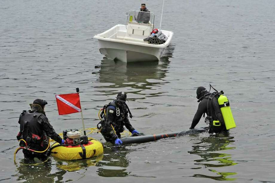 Divers and support members of Aquatic Invasive Management  of Lake Placid prepare to lay a mat on the lake floor to attempt to eliminate Asian Clams that have invaded Lake George, N.Y. April 25, 2011.   (Skip Dickstein / Times Union) Photo: SKIP DICKSTEIN / 00012910A