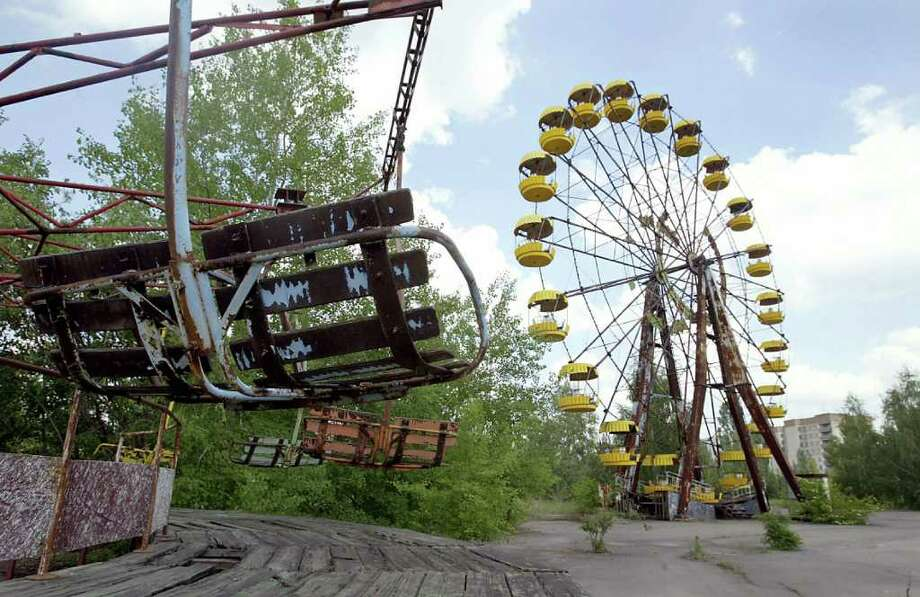 A ferris wheel and a carousel are abandoned 26 May 2003 in the amusement park of the ghost town of Prypyat, adjacent to the Chernobyl nuclear plant. Prypyat which had 45,000 residents was totally evacuated in the first three days after the reactor number four at the Chernobyl plant blew up at 1:23am 26 April 1986, spewing out a radioactive cloud and contaminating much of Europe. An estimated 15,000 to 30,000 people have died in the aftermath.  Over 2,5 million Ukranians suffer from health problems related to the Chernobyl blast, with 80,000 of them receiving a pension. AFP PHOTO/ SERGEI SUPINSKY Photo: SERGEI SUPINSKY, AFP/Getty Images / 2003 AFP
