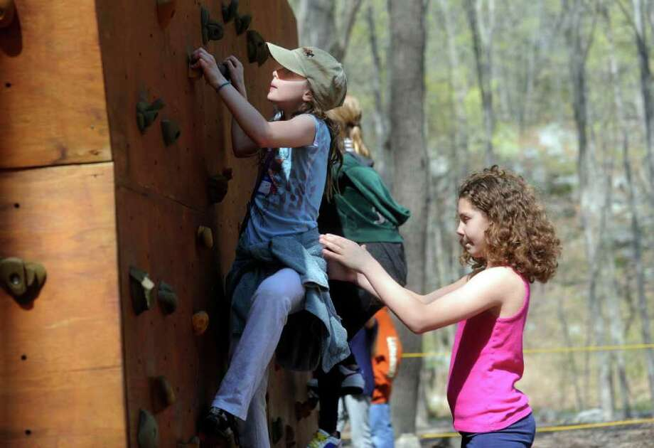 "Kacie Geary, from Parkway School, climbs a wall while Elizabeth Intrier, from North Street Schools, steadies her as Greenwich Public School fifth-graders participated in ""Orienteering Adventure Days"" at Seton Scout Reservation on Tuesday, April 26, 2011 to meet students who will attend their middle schools next year Photo: Helen Neafsey / Greenwich Time"