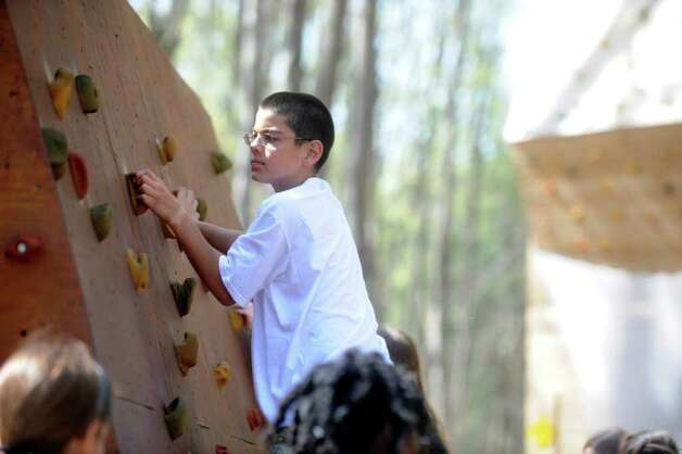 "Jake Pennella from Cos Cob School climbes a wall as Greenwich Public Schools fifth-graders participate in ""Orienteering Adventure Days"" at Seton Scout Reservation on Tuesday, April 26, 2011 to meet students who will attend their middle schools next year. Photo: Helen Neafsey / Greenwich Time"