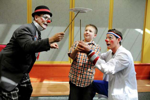 "Ringling Brothers and Barnum and Bailey Circus clowns Joel Jeske, left, and Mike Richter, right, perform a trick with the assistance of Nicholas Tedford, 9, of Coxsackie as they entertain young patients and their families on Tuesday, April 26, 2011, at Albany Medical Center in Albany, N.Y. The ""Greatest Show on Earth"" will be at the Times Union Center from May 5 to 8. (Cindy Schultz / Times Union) Photo: Cindy Schultz"