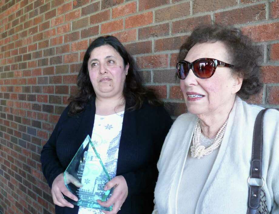"Nadia Guarino, left, holds an award she received from the Fairfield Police Department for helping to keep Rose Mauro, right, from becoming a victim of the ""grandparent scam."" Photo: Genevieve Reilly / Fairfield Citizen"
