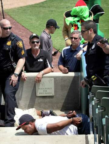 San Antonio police officers detain two San Antonio Missions fans after an altercation between them and members of the Frisco RoughRiders at Wolff Stadium, Tuesday, April 26, 2011. RoughRiders team members threw a bat and a trash can at the fans at the end of the game after the umpire called back a homerun call by the RoughRiders. Photo Bob Owen/rowen@express-news.net Photo: Bob Owen, San Antonio Express-News / rowen@express-news.net