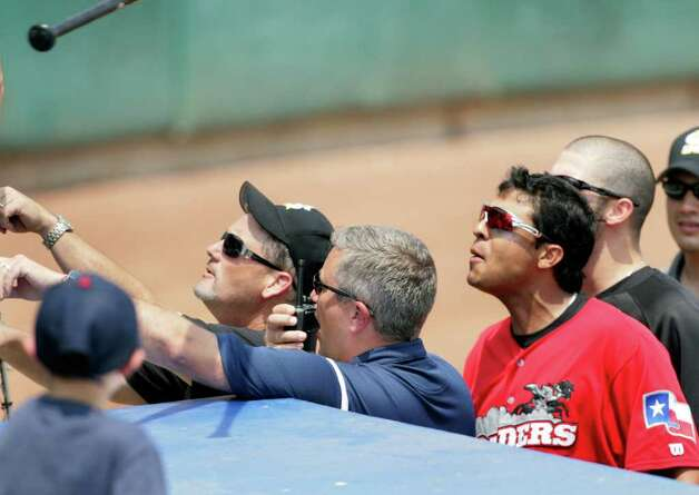 Members of the San Antonio Missions staff, left, try to defuse a scuffle between Missions fans and members of the Frisco RoughRiders, including Guilder Rodriguez, right, after the Missions won the game 6-5 after a controversial call at Wolff Stadium, Tuesday, April 26, 2011. Someone from the dugout threw a bat and a garbage can into the crowd.  Photo Bob Owen/rowen@express-news.net Photo: Bob Owen, San Antonio Express-News / rowen@express-news.net