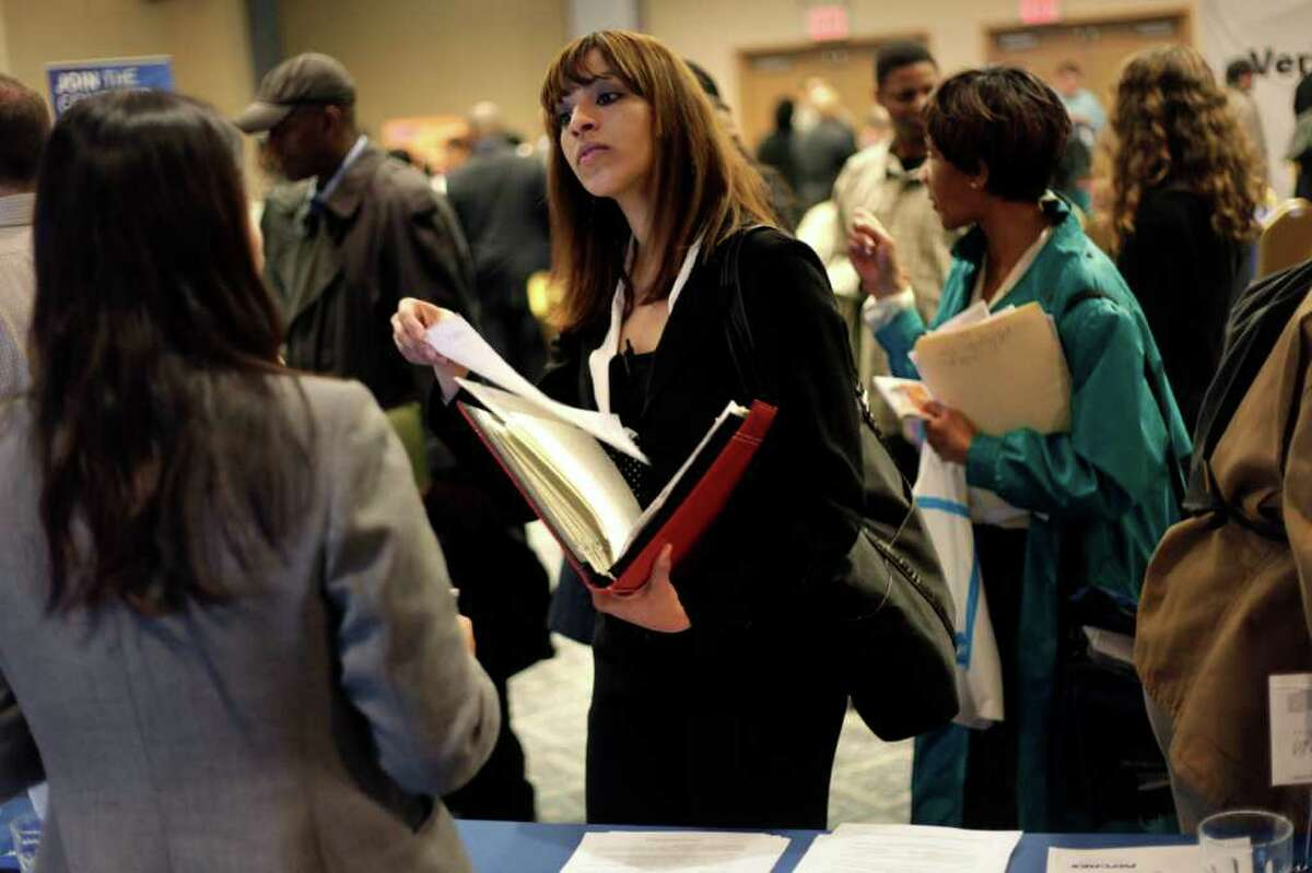 FILE - In this April 18, 2011 file photo, a woman at a job fair in New York talks to an employer. For the first time, American women have passed men in gaining advanced college degrees as well as bachelor's degrees, part of a trend that is helping redefine who goes off to work and who stays home with the kids. (AP Photo/Seth Wenig, File)
