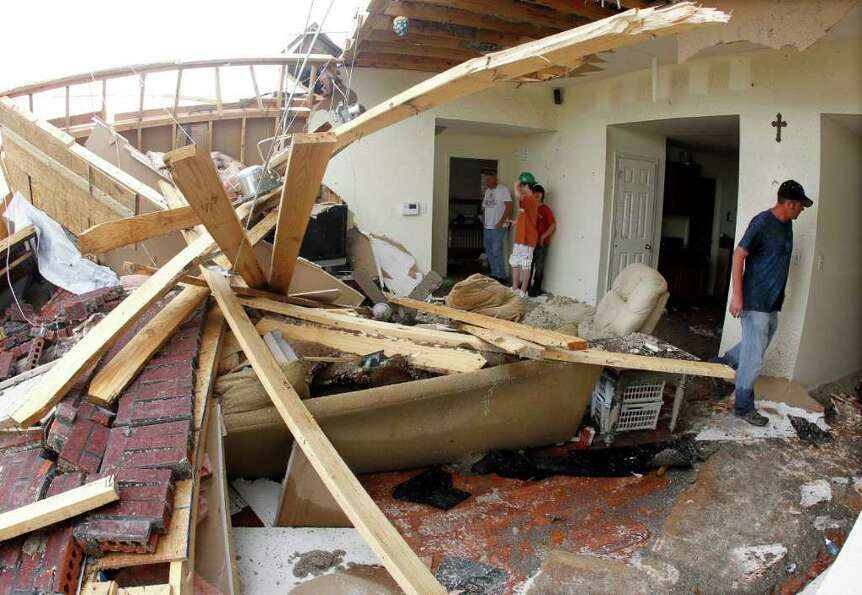 Richard Bass, right, looks over his damaged home on Tuesday, April 26, 2011, in Vilonia, Ark. The to