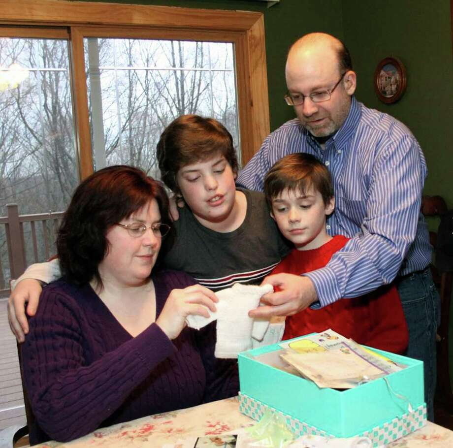 The Matzinger family, from left, includes mom Nancy, 12-year-old Ryan, 8-year-old brother Jacob, and Richard. Here they are looking through a box of Ryan's keepsakes, including his small baby attire. Photo taken Friday, April 22, 2011. Photo: Walter Kidd / The News-Times Freelance