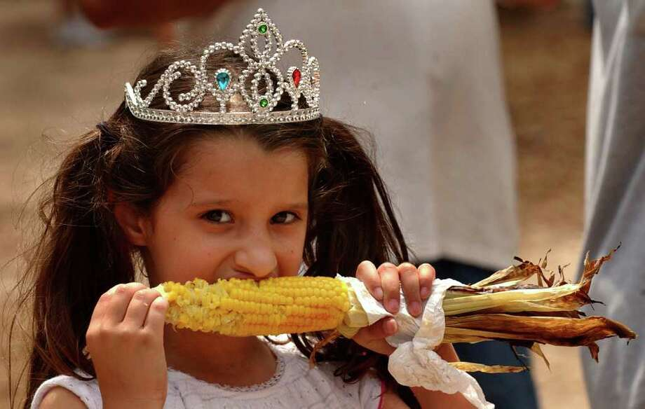Elleanna Martinez, 5, enjoys roasted corn on the cob while sporting a tiara purchased at the 2006 Helotes Cornyval. Photo: GLORIA FERNIZ, SAN ANTONIO EXPRESS-NEWS / SAN ANTONIO EXPRESS-NEWS