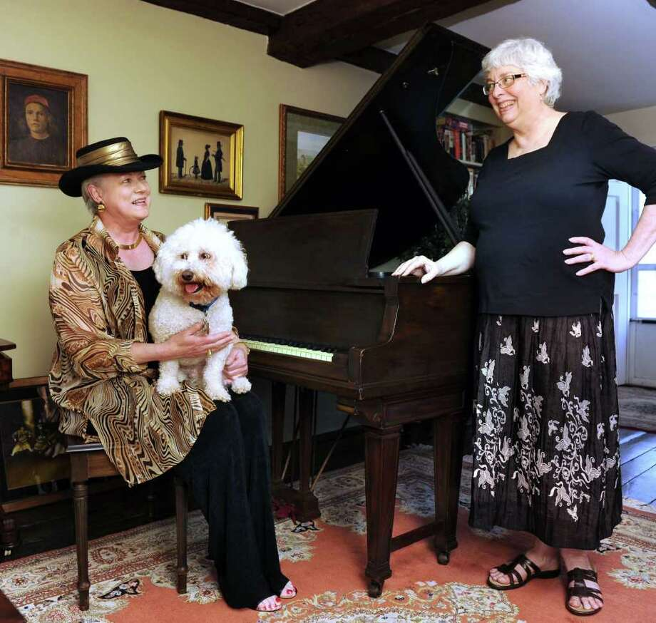 Trisha Lewis, left, vice chairwoman of the Bethel Library board, holding Peanuts, her bichon frise, and Jane Bickford, chairwoman, are photographed with a piano that is being donated to the Bethel Public Library. Photo taken, Tuesday, April 26, 2011. Photo: Carol Kaliff / The News-Times
