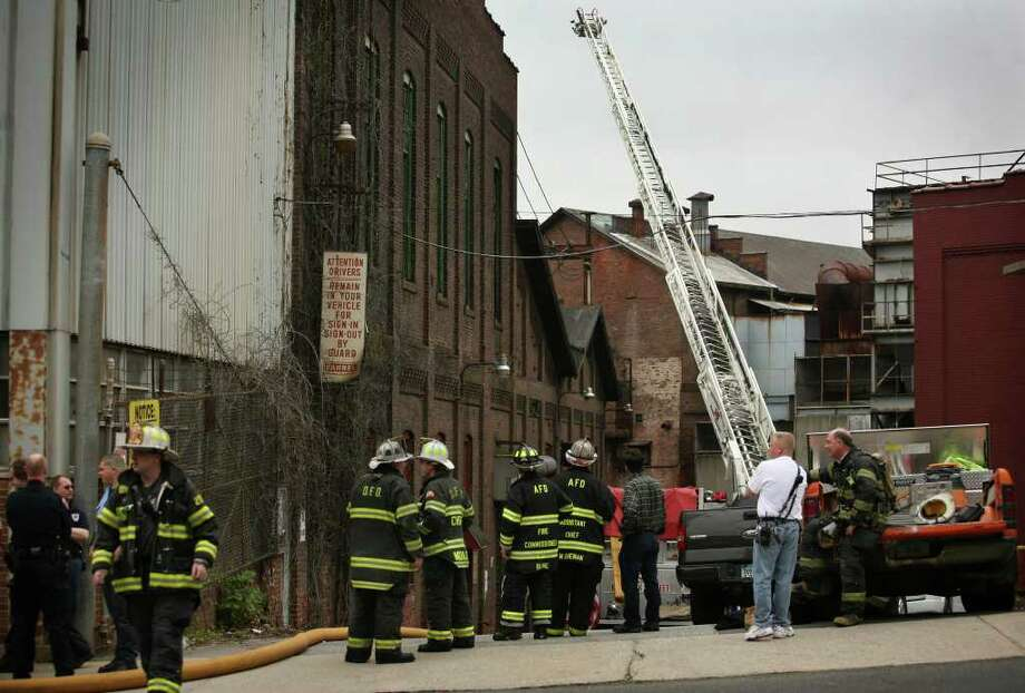 Firefighters in front of the Farrel Corporation factory on Main Street in downtown Ansonia, the scene of a fire on Wednesday, April 27, 2011. Photo: Brian A. Pounds / Connecticut Post