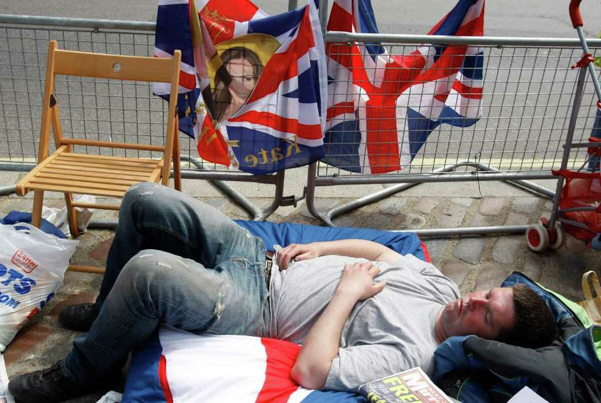A royal fan sleeps on the pavement near to Westminster Abbey in London, Wednesday, April 27, 2011. Royal enthusiasts are camping out outside the Abbey where Prince William and Kate Middleton are due to get married on Friday, April 29. (AP Photo/Kirsty Wigglesworth)