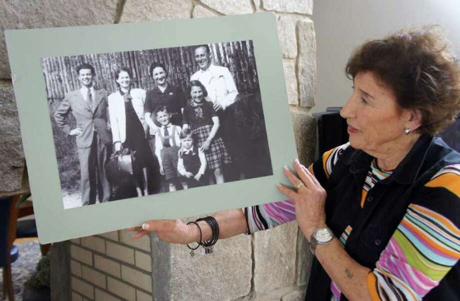 Anita Schorr holds up a picture of her family and another family taken in the spring of 1941. Schorr's father, Fritz, stands at right; her mother, Stella, second from right; her brother, Michael, directly in front of Schorr's mother; and Schorr in front of her father. A few weeks later, Schorr and her family would be deported from their home city of Brno to the town of Terezin, which German forces ran as a Jewish ghetto during World War II. Photo: Paul Schott / Westport News