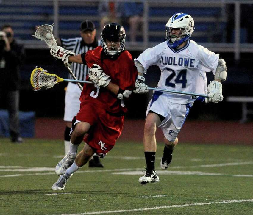 Joe Costigan carries the ball as he is defended by Ludlowe's George Voucas during Wednesday's lacrosse game against New Canaan at Fairfield Ludlowe High School on April 27, 2011.