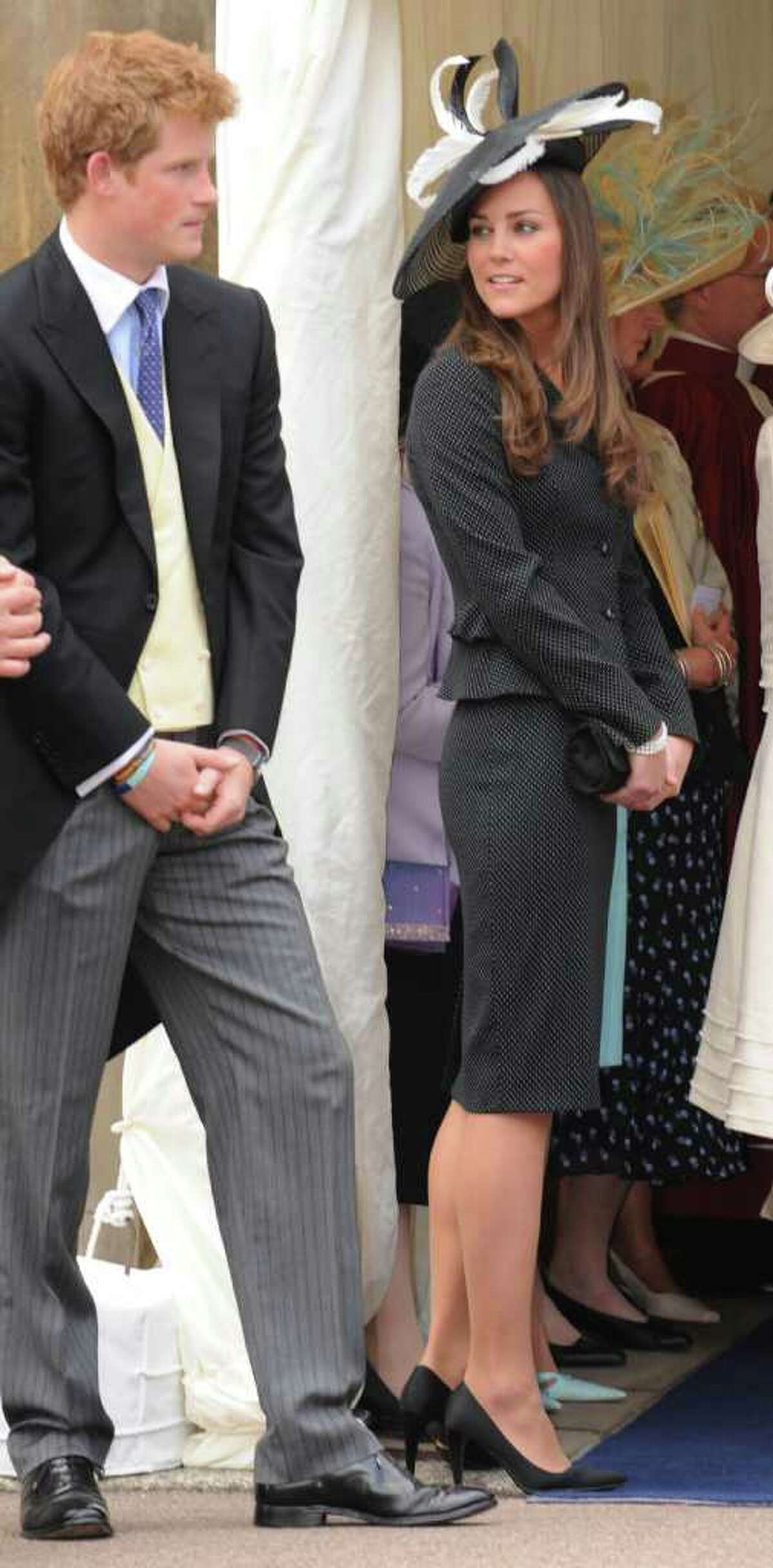 FILE - This is a Monday June 16, 2008 file photo of Kate Middleton as she stands with Britain's Prince Harry attend Order of the Garter ceremony at St George's Chapel, Windsor Castle, England. Will it have sleeves? A sweeping train? Antique lace, or bead work? The questions keep coming, but no one has the answers. Congratulations, Kate Middleton, for keeping your wedding dress the royal wedding's biggest mystery and talking point.(AP Photo/Harry Page, The Daily Mirror, pool, File)