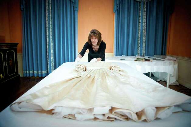 In this undated photo released by the Royal Collection on Thursday April 21 2011, the silk satin wedding dress worn by Queen Victoria in 1840, when she married Albert Saxe-Coburg, is prepared by a conservator for conservation work to begin. As speculation continues as to the design of Catherine Middleton's wedding dress, a precious collection of historic royal wedding dresses worn by royal brides over the last 200 years have just undergone over 1000 hours of conservation treatment by conservators from Britain's Historic Royal Palaces. The wedding dresses belonging to Princess Charlotte (1816), Queen Victoria (1840), Alexandra of Denmark (1863), Princess Mary of Teck (1893), Princess Margaret (1960) and Princess Alexandra of Kent (1963) are usually carefully stored at Kensington Palace but have been made available to the media and are viewable on the Historic Royal Palaces website. (AP Photo/The Royal Collection/Historic Royal Palaces) MANDATORY CREDIT.  NO ARCHIVE NO SALES.  SINGLE USE AND IN RELATION TO THE ROYAL WEDDING ONLY Photo: Richard Lea-Hair