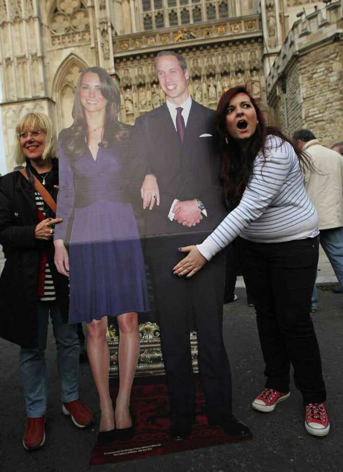 LONDON, ENGLAND - APRIL 28:  An Italian tourist extends her hand over her idea of the Royal Jewels next to a cardbaord mock up of Prince William and Kate Middleton outside Westminster Abbey a day ahead of the Royal Wedding on April 28, 2011 in London, England. Millions of people the world over are expected to watch live broadcasts of the wedding on television in what is becoming the most talked about event of the year.  (Photo by Sean Gallup/Getty Images) Photo: Getty Images