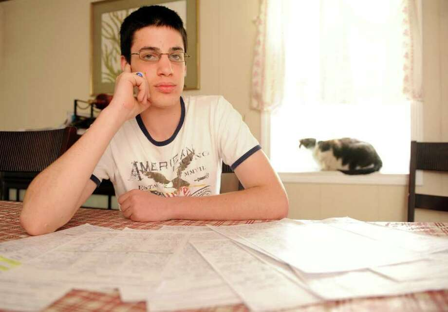 Fifteen-year-old Masuk student Anthony Casertano sits with the hundreds of signatures he collected laid out before him at his home in Monroe.  Casertano organized a petition to oppose Planning and Zoning's recent approval of a second McDonald's restaurant in Monroe. Photo: Autumn Driscoll / Connecticut Post