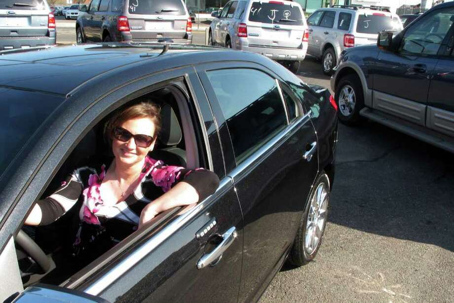 Stacey Kamienski of Newington, takes delivery of a shiny black Lincoln MKZ Hybrid at Park City Ford in Bridgeport, Conn. April 26th, 2011. The Lincoln can get 41 mpg in city driving. Kamienski traded in her 13 mpg, 5,300-pound Ford Expedition, seen here to the right. Photo: John Burgeson / Connecticut Post