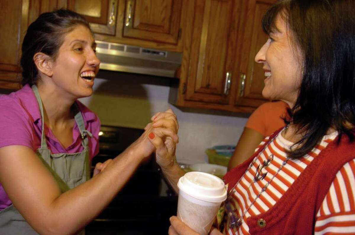 Brita Darany von Regensburg, right, the founder of Friends of Autistic People, a Greenwich-based nonprofit organization for adults with autism, and her daughter, Vanessa Darany, who has autism, lives at a group home in Trumbull, play a form of patty cake while the mother visits the home in Trumbull on Aug. 13, 2010.