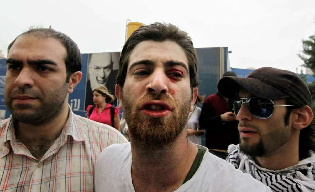 A Lebanese demonstrator, center, argues with police after he was beaten as protesters tried to block a road during a sit-in against the sectarian makeup of Lebanon's government, in Beirut, Lebanon, Thursday, April 28, 2011. (AP Photo/Bilal Hussein)