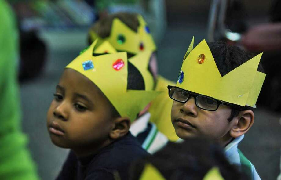 Tejas Kilaru, 4, right, and fellow pre k students wear crowns they made, while listening to Lisa Witkowski read the story of Cinderella's wedding at Mater Christi School on Thursday April 28, 2011 in Albany, NY.  She linked Friday's upcoming royal wedding of Prince William and Kate Middleton with the Princess story she was reading.  She is the school's pre k and kindergarten librarian. ( Philip Kamrass / Times Union ) Photo: Philip Kamrass
