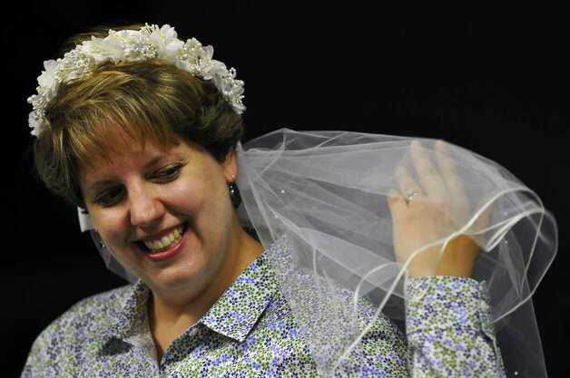 Lisa Witkowski wore the bridal veil from her 1994 wedding while reading the story of Cinderella's wedding to pre k students at Mater Christi School on Thursday April 28, 2011 in Albany, NY.  She linked Friday's upcoming royal wedding of Prince William and Kate Middleton with the Princess story she was reading. She watched the 1981 wedding of Prince Charles and Diana Spencer on tv, when she was in high school. She is the school's pre k and kindergarten librarian. ( Philip Kamrass / Times Union ) Photo: Philip Kamrass