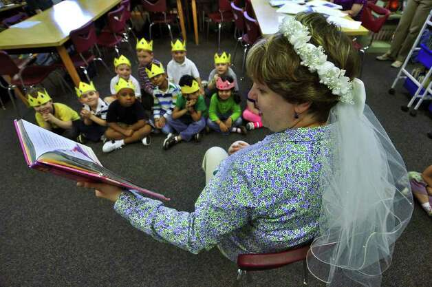 Lisa Witkowski wears the bridal veil from her 1994 wedding while reading the story of Cinderella's wedding to pre k students at Mater Christi School on Thursday April 28, 2011 in Albany, NY.  She linked Friday's upcoming royal wedding of Prince William and Kate Middleton with the Princess story she was reading. She watched the 1981 wedding of Prince Charles and Diana Spencer on tv, when she was in high school. She is the school's pre k and kindergarten librarian.  ( Philip Kamrass / Times Union ) Photo: Philip Kamrass
