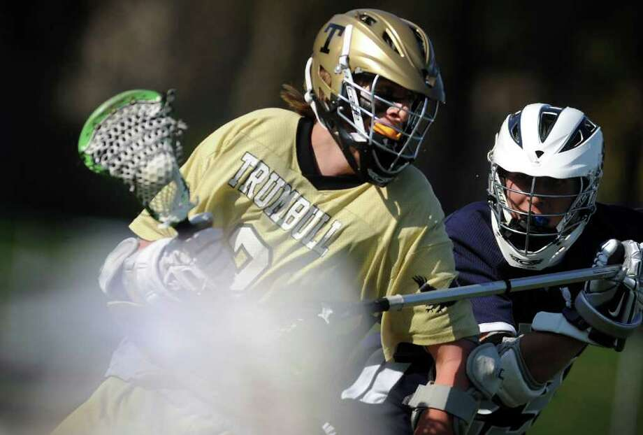 Trumbull's Patrick Lomnitzer controls the ball as Staples' Kosta Papa defends during Tuesday's lacrosse match at Trumbull High School. Photo: Autumn Driscoll / Connecticut Post