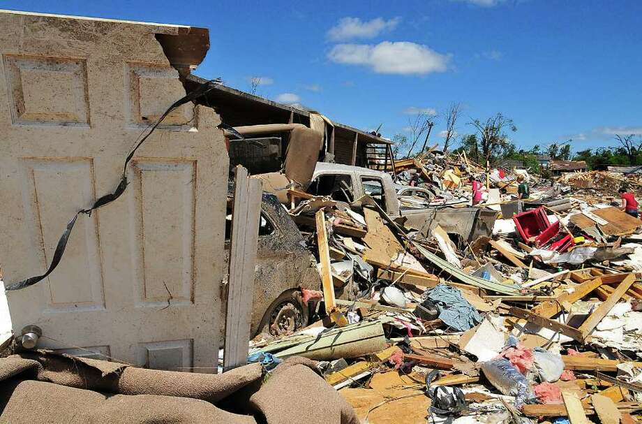 People look for their belongings in the Alberta City neighborhood Thursday April 28, 2011, after a tornado struck Tuscaloosa, Ala. the day before. Massive tornadoes tore a town-flattening streak across the South, killing at least 269 people in six states and forcing rescuers to carry some survivors out on makeshift stretchers of splintered debris.  (AP Photo/David Bundy) Photo: David Bundy