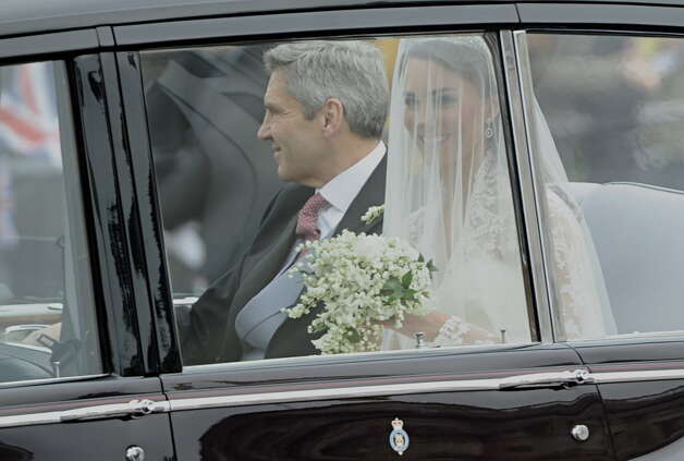 Kate Middleton, right, travels in a Rolls Royce Phantom VI, accompanied by her father Michael Middleton to Westminster Abbey in London for her wedding to Britain's Prince William, on April 29, 2011. (AFP PHOTO / PIERRE-PHILIPPE MARCOU)