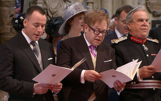 Elton John, center, and his partner David Furnish, left, sing during the ceremony at Westminster Abbey for the Royal Wedding in London on Friday, April, 29, 2011. (AP Photo/APTN)