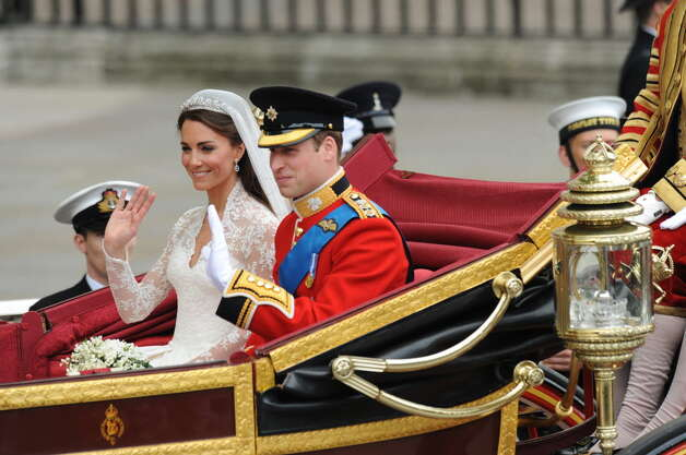 Britain's Prince William and his wife Kate, Duchess of Cambridge, wave as they travel in the 1902 State Landau carriage along the Processional Route to Buckingham Palace, in London, on April 29, 2011. (BEN STANSALL/AFP/Getty Images)