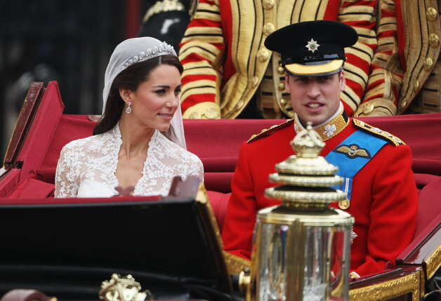 LONDON - APRIL 29: Their Royal Highnesses Prince William Duke of Cambridge and Catherine Duchess of Cambridge make the journey by carriage procession to Buckingham Palace following their marriage at Westminster Abbey on April 29, 2011 in London, England. The marriage of the second in line to the British throne was led by the Archbishop of Canterbury and was attended by 1900 guests, including foreign Royal family members and heads of state. Thousands of well-wishers from around the world have also flocked to London to witness the spectacle and pageantry of the Royal Wedding. (Photo by Dan Kitwood/Getty Images)