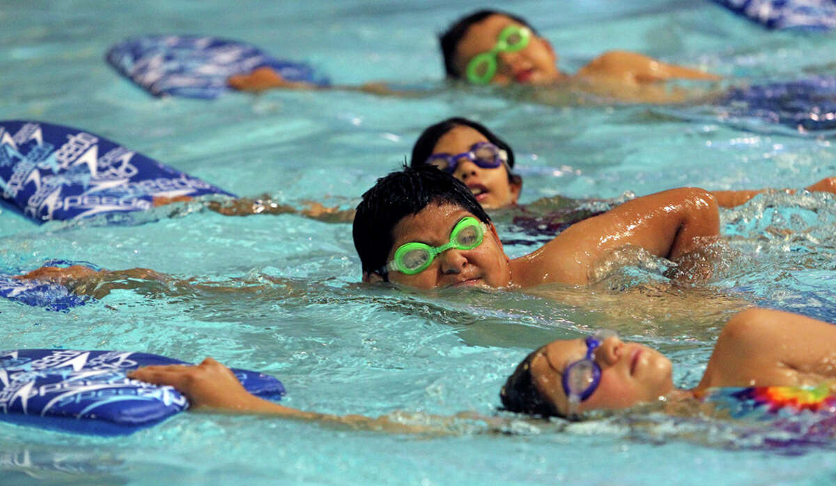Seth Almendarez (second from bottom) puts effort into a drill during a basic swimming session for kids at Calderon Branch Boys & Girls Club. TOM REEL / EXPRESS-NEWS