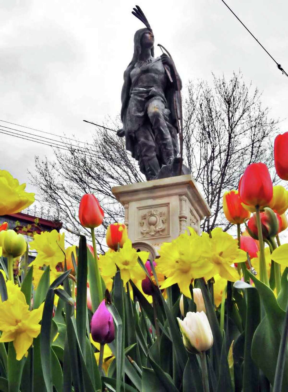 """Spring flowers in bloom around the statue of """"Lawrence the Indian"""" in Schenectady's historic Stockade neighborhood Friday afternoon April 29, 2011. (John Carl D'Annibale / Times Union)"""