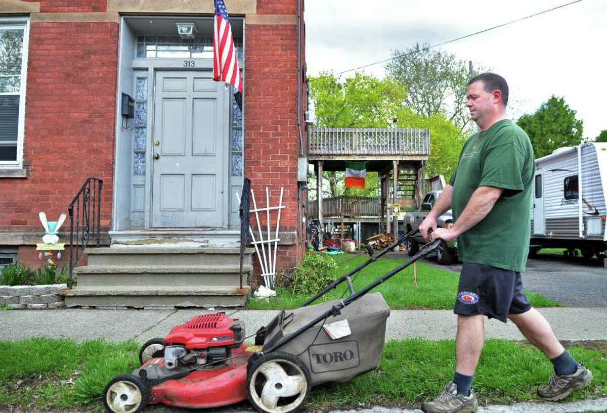 Jim Conlen mows the lawn at his Watervliet home on Friday, April 29, 2011. (John Carl D'Annibale / Times Union)
