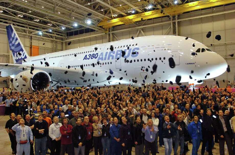 Airbus employees throw their caps in the air next to the first Airbus A380 after its unveiling ceremony, near Toulouse, southwestern France, Tuesday Jan.18, 2005. Photo: CHRISTOPHE ENA, Associated Press / AP