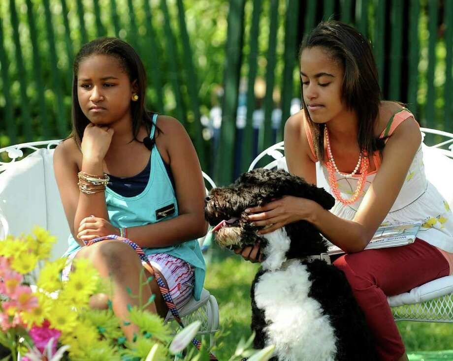 Sasha Obama and Malia Obama play with their dog Bo as they listen to President Barack Obama read to children during the White House Easter Egg Roll on the South Lawn of the White House on April 25, 2011 in Washington, DC. About 30,000 people are expected to attend the 133-year-old tradition of rolling colored eggs down the White House lawn. Photo: Getty Images