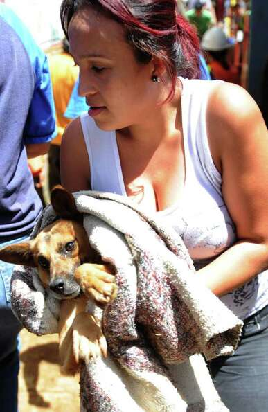 A woman holds a dog rescued among rubble after a landslide in Santo Domingo Savio neighborhood, east