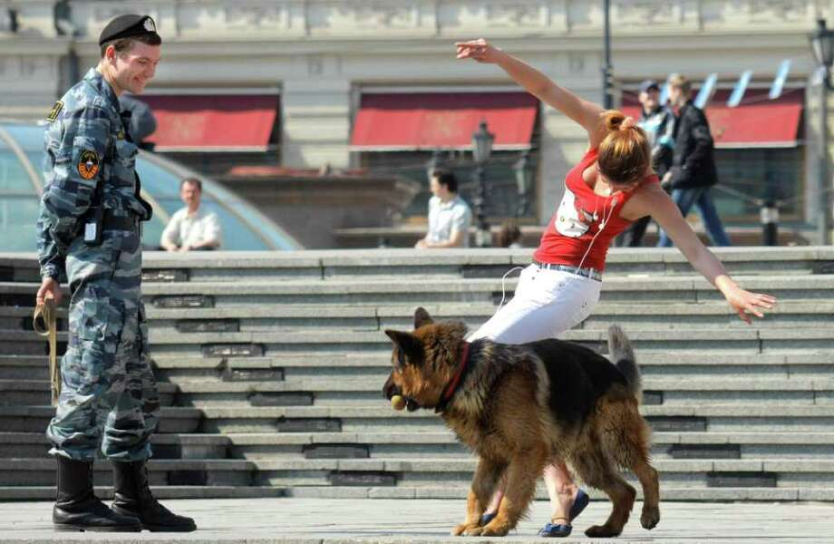 A young woman plays with a police dog as a police officer looks on in downtown Moscow, Russia, Wednesday, April 27, 2011.  Photo: Mikhail Metzel, ASSOCIATED PRESS / AP2011