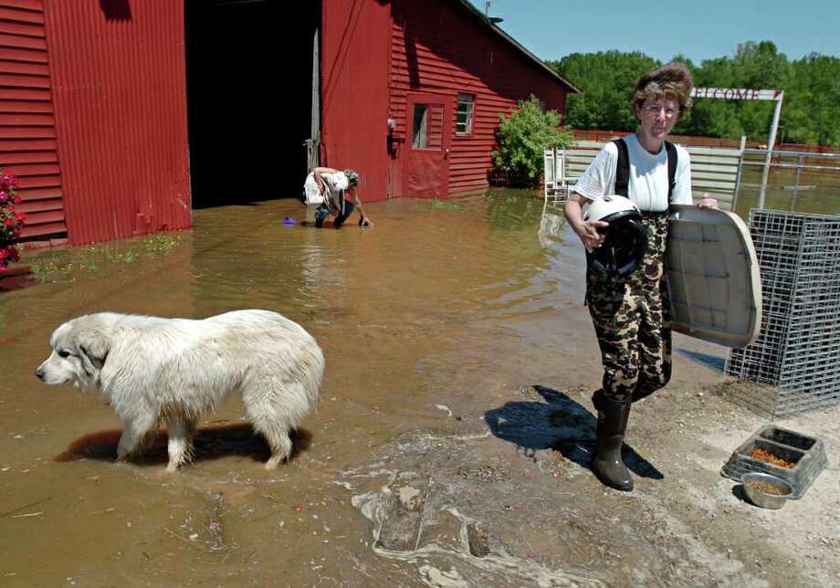 Melissa Floyd gathers her horse riding gear from her flooded barn at the Downtown Dogs Group in Jackson, Tenn. on Friday, April 29, 2011. Photo: AP