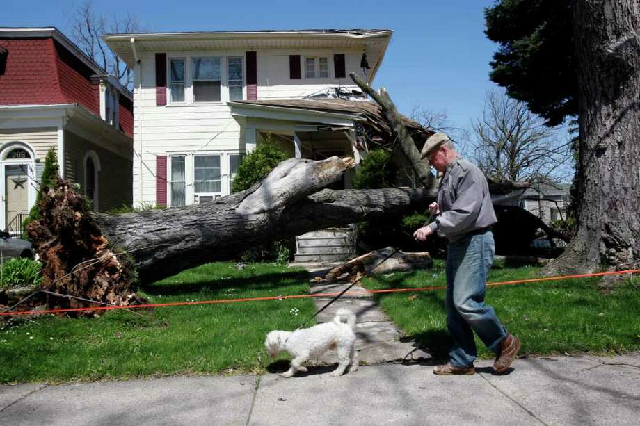Allan Jack walks his dog Buzz while surveying the damage from fallen trees in his neighborhood during high winds in Lockport, N.Y., Thursday, April 28, 2011. Photo: AP