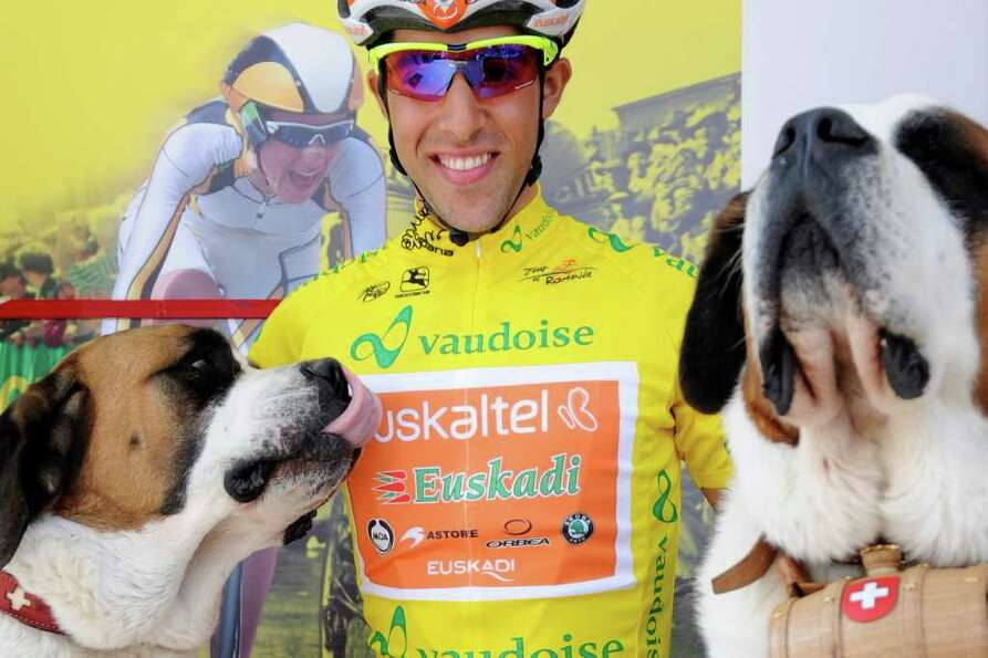 The overall leader Spain's Jonathan Castroviejo of team Euskatel poses with Saint-Bernard dogs befor