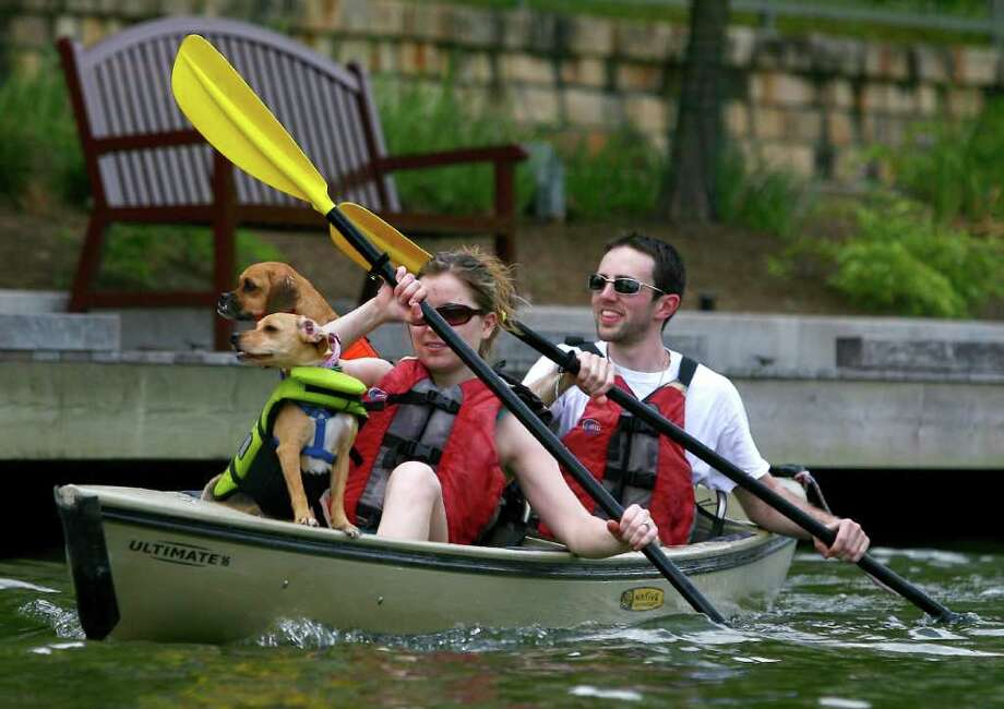 Kacie Broadhurst and Joe Pattavina, of The Woodlands, Texas,  enjoy sunny skies and warm weather as they paddle on The Woodlands Waterway with their dogs, Carmella and Annie, on Sunday, April  24, 2011. Photo: AP