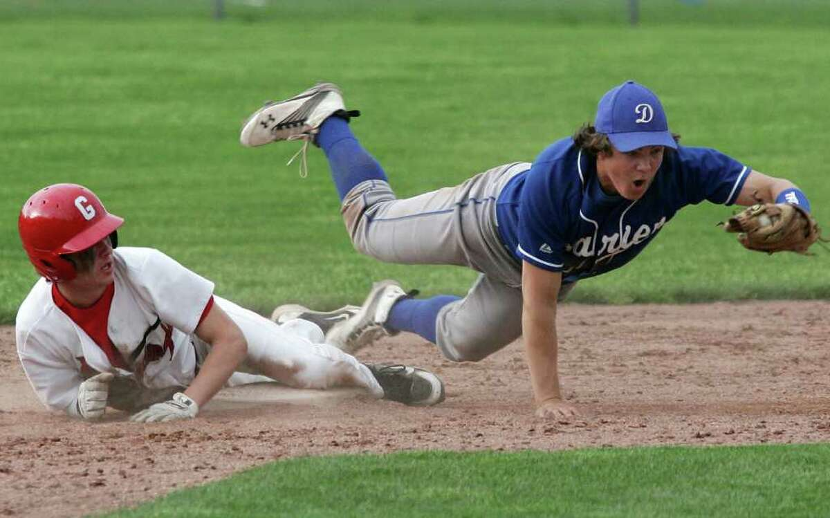 Darien's second baseman Tommy Farren was unable to make the tag on Greenwich's Dylan Callahan who went on to score the winning run in Friday's extra innings game in which the Cardinal's went on to win 6-5.