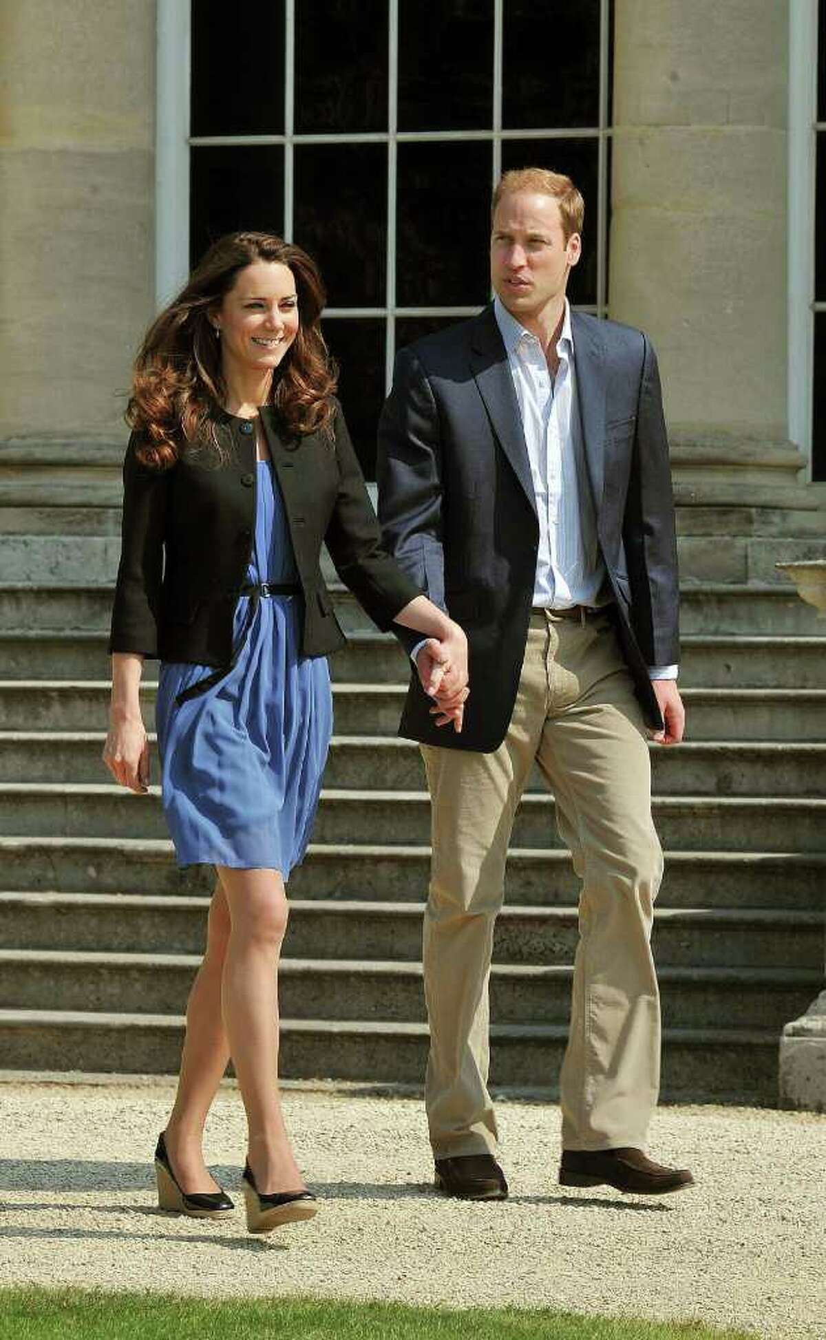 The Duke and Duchess of Cambridge walk hand in hand from Buckingham Palace in London Saturday April 30 2011, the day after their wedding. (AP Photo/ John Stillwell, pool)
