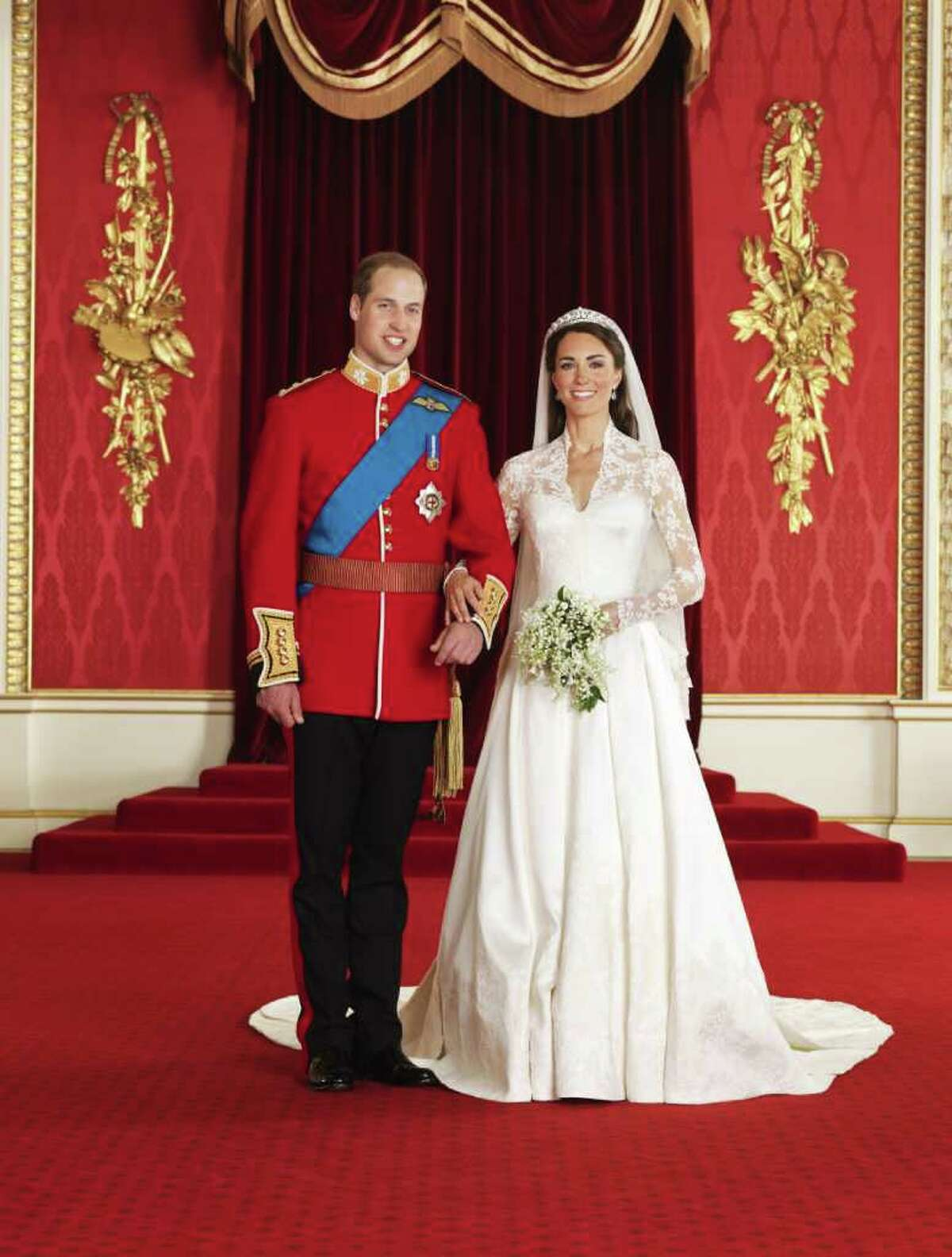 In this photo provided by Clarence House on Saturday April 30 2011, Britain's Prince William, left, and his wife Kate, Duchess of Cambridge, pose for a photograph in the throne room at Buckingham Palace, following their wedding at Westminster Abbey, London, on Friday, April 29. (AP Photo/Hugo Burnand, Clarence House) NO SALES