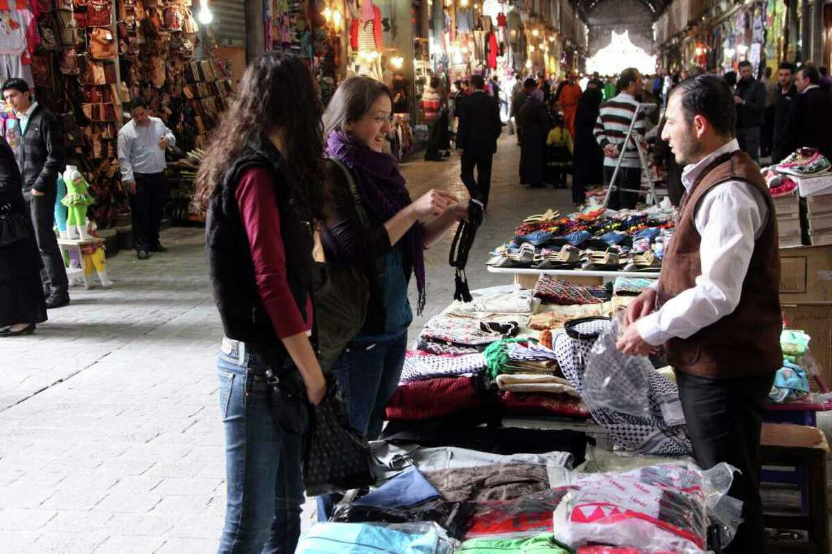 Women talk to a vendor as they shop in a market in old Damascus, Syria, Saturday, April 30, 2011, pictured on a government-provided tour. Syrian army troops backed by tanks and helicopters on Saturday took a prominent mosque that had been controlled by residents in a besieged southern city, killing four people, a witness said. (AP Photo/Bassem Tellawi)