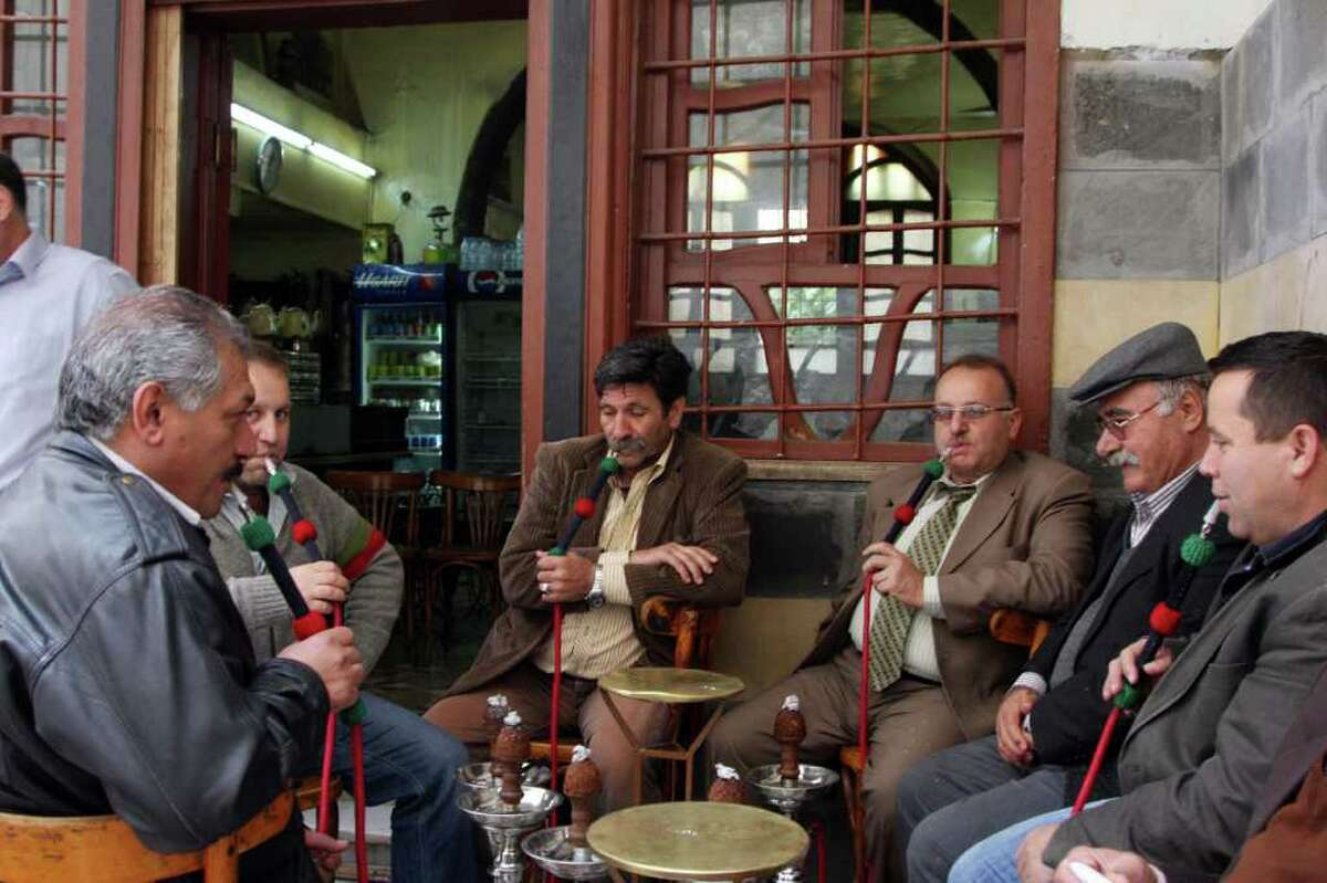 Syrian men smoke waterpipes as they sit in a cafe in old Damascus, Syria, Saturday, April 30, 2011 photographed on a government-provided tour. Syrian army troops backed by tanks and helicopters on Saturday took a prominent mosque that had been controlled by residents in a besieged southern city, killing four people, a witness said. (AP Photo/Bassem Tellawi)