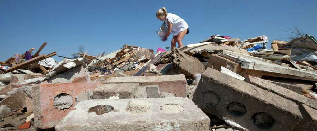 Volunteer Rachel Shugart searches the rubble for valuables in Tuscaloosa, Ala., Saturday, April 30, 2011. Hundreds of people were killed when tornadoes swept across six states on Wednesday. (AP Photo/Dave Martin)